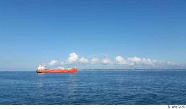Un bateau rouge sur la mer, ciel bleu - © Luan Goes